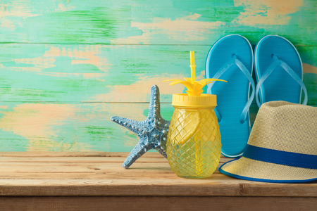 Summer background with refreshing drink in pineapple jar, hat and flip flops on wooden table