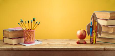 Fondo de regreso a la escuela con cohete hecho de lápices, manzana y libros antiguos sobre pared amarilla