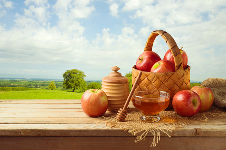 Honey and apples on wooden table over nature landscape background