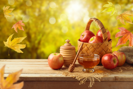 Honey and apples on wooden table. Autumn and fall harvest background