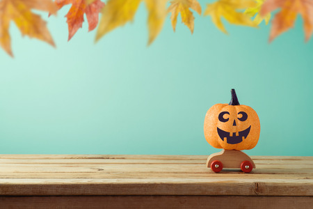 Halloween holiday concept with jack o lantern glitter pumpkin decor on toy car over autumn background