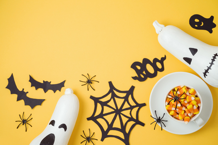Halloween holiday background with jack o lantern pumpkin, candy corn and decorations. View from above. Flat lay Stock Photo