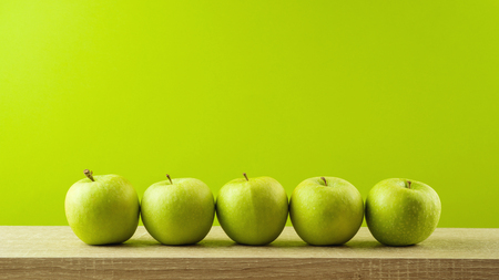 Jewish holiday Rosh Hashanah background with green apples on wooden table.