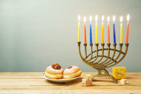 Jewish holiday Hanukkah background with sufganiyot and menorah on wooden table
