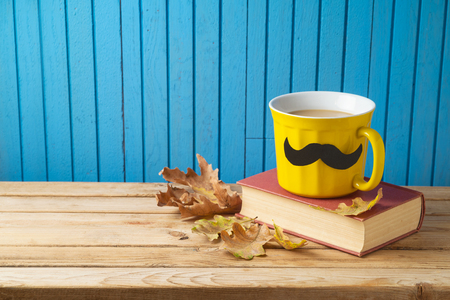 Autumn and Movember concept with coffee cup and mustache on wooden background