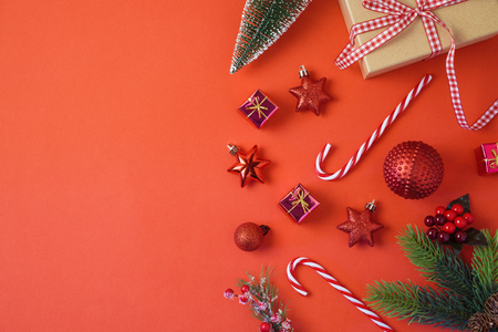Christmas holiday background with decorations and ornaments on red table. Top view from above