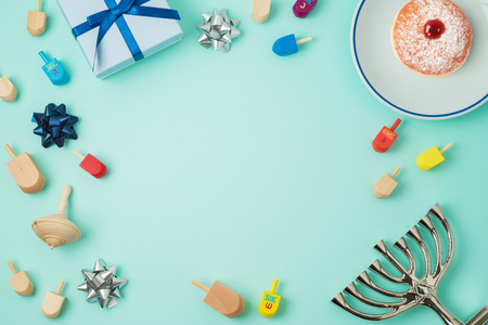 Jewish holiday Hanukkah background with menorah, sufganiyot, gift box and spinning top. Top view from above. Flat lay
