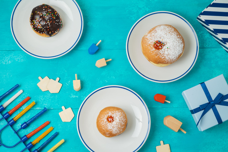 Jewish holiday Hanukkah concept with menorah, sufganiyot, gift box and spinning top. Top view from above. Flat lay