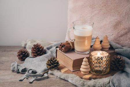 Hygge Scandinavian style concept with latte macchiato coffee cup, candles and book. Cozy winter or Christmas composition