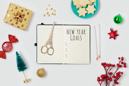 New Year resolutions concept with notepad and gift boxes on white background. Top view from above. Flat lay Stock Photo - 115169056