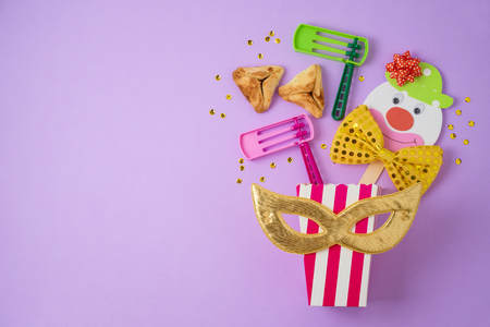 Jewish holiday Purim background with carnival mask, paper clown and hamantaschen cookies. Top view from above. Flat lay Stock Photo