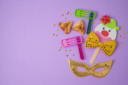 Jewish holiday Purim background with cute paper clowns character, hamantaschen cookies and carnival mask. Top view from above. Flat lay