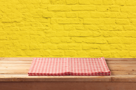 Empty wooden table with tablecloth over yellow brick stone wall background.