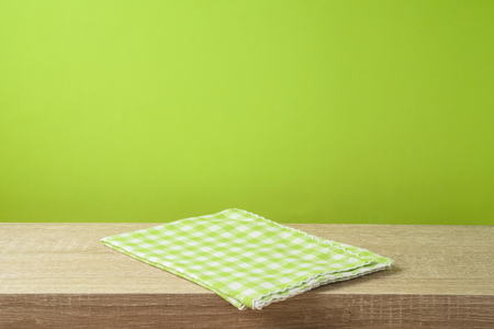 Empty wooden table with tablecloth over green wall  background.