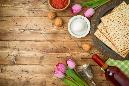 Jewish holiday Passover background with matzo, seder plate, wine and tulip flowers on wooden table. Top view from above.  Stock Photo