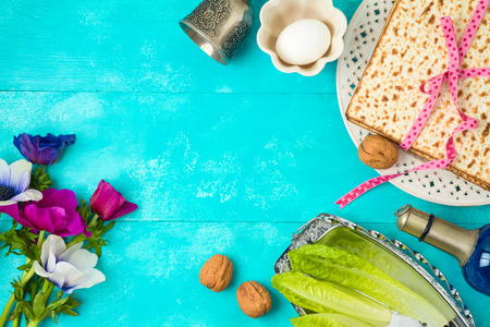 Jewish holiday Passover background with matzo, seder plate and spring flowers on wooden table. Top view from above.