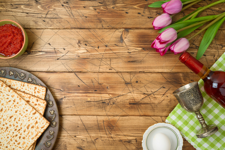 Jewish holiday Passover background with matzo, seder plate, wine and tulip flowers on wooden table. Top view from above.  Archivio Fotografico