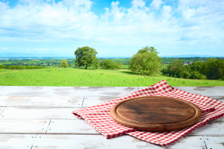 Empty wooden table with round board and tablecloth over summer meadow background