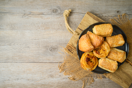 Burekas filled with cheese, potato and pizza rolls on wooden table. Top view from above