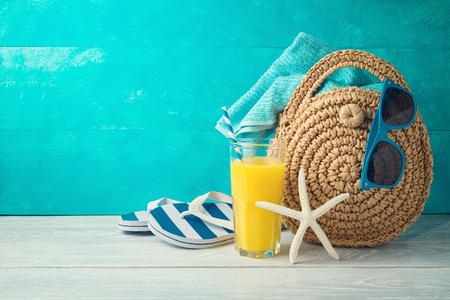 Fondo de vacaciones de vacaciones de verano con jugo de naranja, bolso de moda de playa y chanclas en mesa de madera