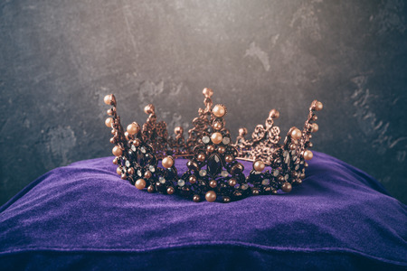 Fairy tale crown on pillow over dark background. Medieval period concept