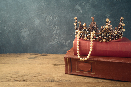 Fairy tale crown and old books on wooden table over dark background. Medieval period concept
