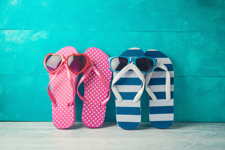 Summer concept background with cute funny flip flops and sunglasses on wooden table 写真素材