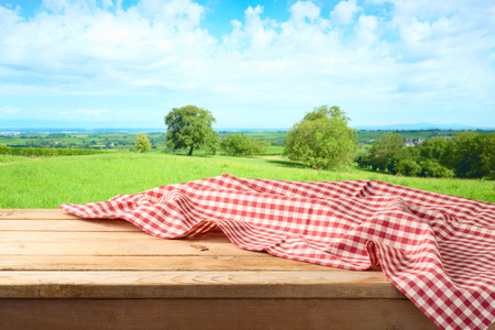 Empty wooden table with tablecloth over summer meadow background