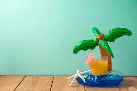 Summer vacation background with orange juice and pool float on wooden table