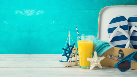 Summer concept background with cute funny flip flops, suitcase and orange juice on wooden table