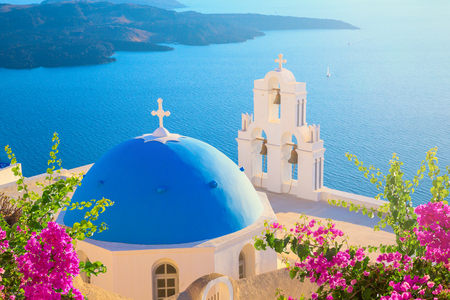 Santorini island, Greece. Thera (Fira) town traditional white houses and churches with blue domes over the Caldera, Aegean sea.