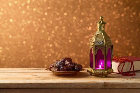 Lightened lantern and dates fruit on wooden table over bokeh background. Islamic holiday celebration concept