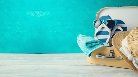 Summer concept background with cute funny flip flops, suitcase and hat on wooden table