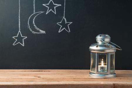 Lightened lantern on wooden table over blackboard background. Islamic holiday celebration concept 写真素材