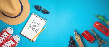 Concept de voyage et de tourisme avec accessoires de voyage et souvenirs du monde entier sur fond bleu. Vue de dessus d'en haut