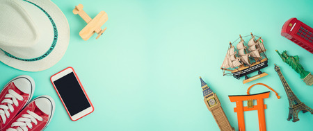 Travel and tourism concept with traveling accessories and souvenirs on blue background. Top view from above