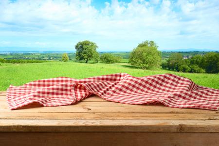Mesa de madera vacía con mantel sobre fondo de pradera de verano