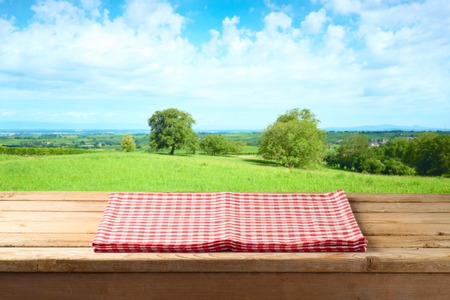 Lege houten tafel met tafelkleed over zomer weide achtergrond Stockfoto