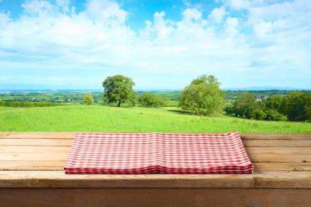 Mesa de madera vacía con mantel sobre fondo de pradera de verano Foto de archivo