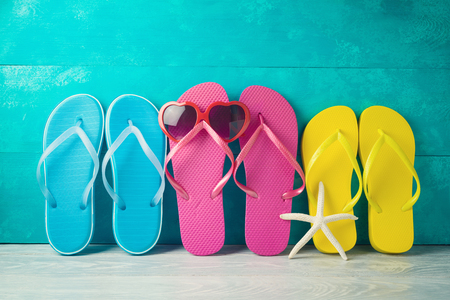 Summer concept background with cute funny flip flops and sunglasses on wooden table. Family vacation concept 写真素材