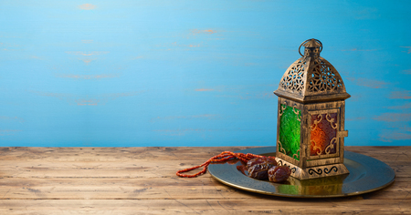 Lightened lantern and dates fruit on wooden table over blue background. Islamic holiday celebration concept 写真素材