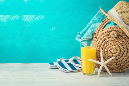 Summer holiday vacation background with orange juice, beach fashion bag and flip flops on wooden table