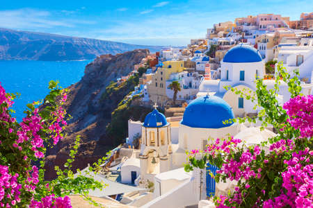 Santorini island, Greece. Oia town traditional white houses and churches with blue domes over the Caldera, Aegean sea. Imagens