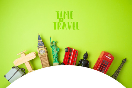 Travel and tourism concept with souvenirs from around the world on green  background. Top view from above