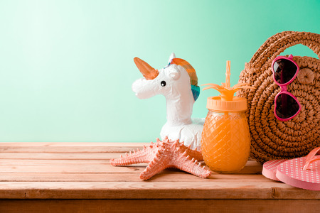 Summer vacation concept with pineapple juice, beach accessories and unicorn pool float on wooden table background