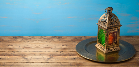 Lightened lantern on wooden table over blue background. Islamic holiday celebration concept