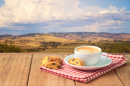 Coffee cup with italian biskotti cookies on wooden table over Tuscany landscape background