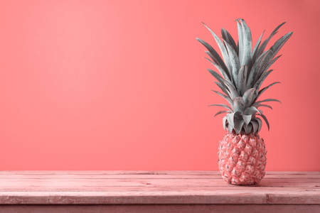 Summer concept with pineapple on wooden table over coral color background 写真素材