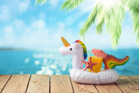 Summer vacation concept with orange juice and unicorn pool float over sea beach background 写真素材