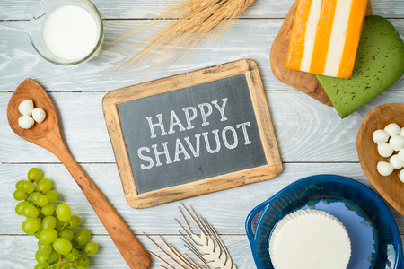 Milk and dairy products on wooden background. Jewish holiday Shavuot concept. Top view from above